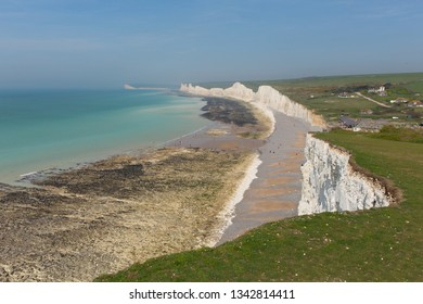 Birling gap beach and Seven Sisters white chalk cliffs East Sussex England UK with sea out