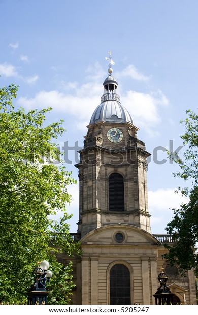 Birmingham city cathedral framed by trees with blue sky background