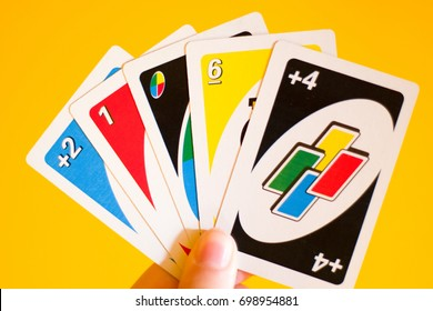 BIRMINGHAM, ENGLAND, AUGUST 18TH 2017, Uno game cards in female hand. American card game, yellow background.