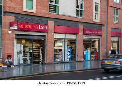 Birmingham, England - March 17 2019:   A Homeless man sits by the Entrance to Sainsbury's local supermarket on Navigation Street