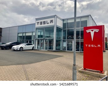 Birmingham, Great Britain - May 27, 2019: Tesla Dealership with Tesla Model S and Model X electric cars parked in the showroom and in front of the building.