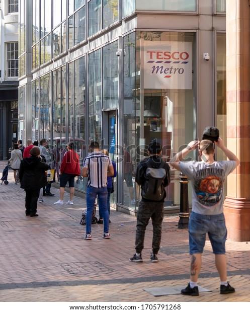 BIRMINGHAM, UK - 2020: A long queue of people social distancing at Tesco supermarket in Birmingham city centre during coronavirus pandemic