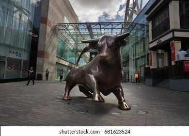 BIRMINGHAM, UK - 20.7.17 : The Guardian, a (7 ft 3 in) tall bronze sculpture of a running, turning bulL, created by Laurence Broderick stands at the entrance of the Bull Ring shopping center.