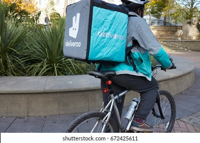 Birmingham, UK - 6 November 2016: Food Delivery Person Wearing Backpack Riding Bicycle