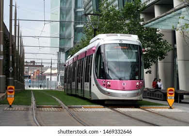 Birmingham, UK - August 03 2019: Network West Midlands Metro. Pink, white and silver tram driving through Snow Hill