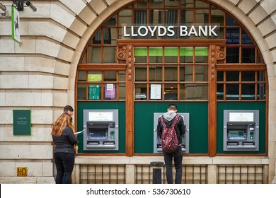 BIRMINGHAM, UK - DECEMBER 11, 2016: People at Lloyds bank atm, cash dispenser