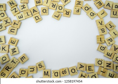 Birmingham, UK - December 2018: Scrabble letters around the edge of the frame with blank white copy space