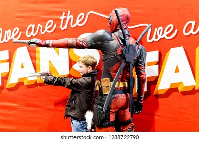 Birmingham, UK - March 17, 2018. Young boy comicon fan poses pointing gun with Marvel Comics character Deadpool in cosplay fancy dress at a comic convention.