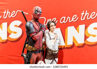 Birmingham, UK - March 17, 2018. Young female comicon fan poses with Marvel Comics character Deadpool in cosplay fancy dress at a comic convention in the UK