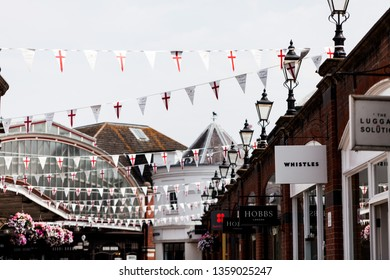 BIRMINGHAM, UK - March 2018 Celebrate the Anniversary of Windsor Royal Shopping. Branded Luxury Shops Lining Up on One Side. White Bunting with Red Cross Hanging above Across the Path.
