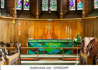 BIRMINGHAM, UK - March 2018 Chancel Area in Church for Choir and Clergy. Stained Glass and Wood Panel Wall as Backdrop. Celtic Cross and Candlestick Holder with Candle on Altar Table.