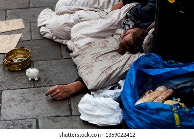 BIRMINGHAM, UK - March 2018 Rough Sleeper Lying Down on Cold Pavement with His Belongings. Piggy Bank beside Tin Container for Money Given by Passersby. Homeless Beggar Needing Care.