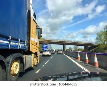 Birmingham, UK: May 02, 2018: Roadworks and congestion on a major UK Highway. Large trucks caught in the congestion caused by road maintenance and repair on the busy M6 motorway.