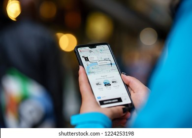Birmingham, UK - October 13, 2018: Person using the Uber Taxi App in the streets of Birmingham, England