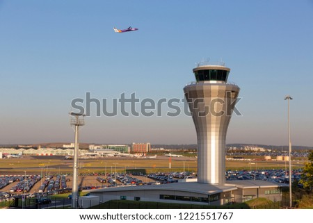 BIRMINGHAM, UK - OCTOBER 17, 2018: General wide view of Birmingham Airport in the Midlands, England with a Flybe aircraft passing the distinctive, metallic control tower.
