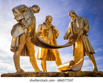 BIRMINGHAM, UK - SEPTEMBER 11, 2016: Boulton Watt and Murdoch Statue by William Bloye and Raymond Forbes-Knight in Gilded Bronze on Portland Stone in Broad St Birmingham with Blue Sky and White Cloud