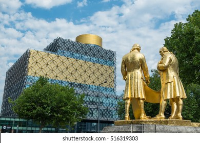 BIRMINGHAM, UK - SEPTEMBER 2016: Golden Boulton, Watt and Murdock statue in front of the Library of Birmingham, England.