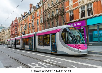 BIRMINGHAM, WEST MIDLANDS, ENGLAND, July 2016. A modern pink and grey tram in the city centre.