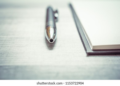 Biro Beside An Empty Notepad On A Table