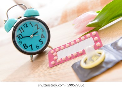 Birth control, contraceptive pills and condoms with clock in bedroom