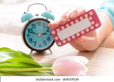 Birth control, contraceptive pills in hand with clock in bedroom