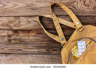 The birth control pill and condom falls out of pocket with handbags on wooden background. Toned image.