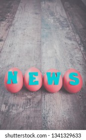 "Birth of the news: four eggs with ""news"" word on wooden background, copy space"