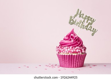 Birthday background with celebration cupcake with happy birthday banner on a pink background