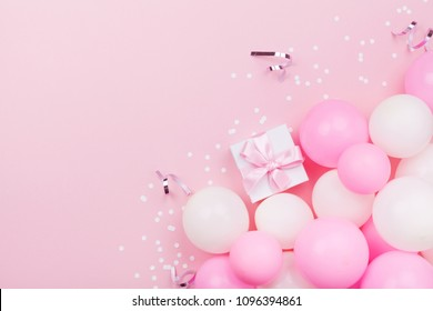 Birthday background with gift or present box, balloons and confetti on pink pastel table from above. Flat lay style.