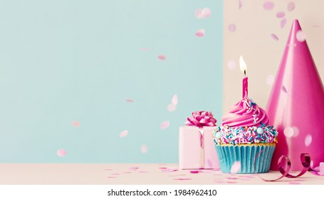 Birthday background with pink birthday cupcake and candle, birthday gift and party hat