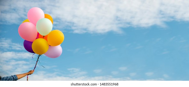 Birthday balloon Holding by Happy child in summer carnival.Colorful of multicolored balloons floating in blue sky banner background with copy space,vintage filter effect.Freedom concept.