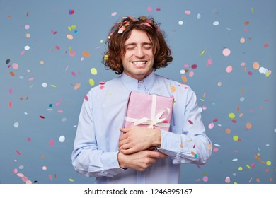 Birthday boy with eyes closed, presses the gift box tied with a white ribbon to himself,is grateful happy, enjoys moment, confetti falls on him,stands isolated on a blue background, feels happiness