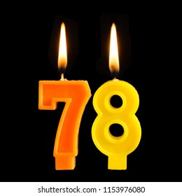 Birthday burning candles in the form of 78 seventy eight for cake isolated on black background.