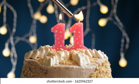 Birthday cake with 11 number candle on blue backgraund set on fire by lighter. Close-up view