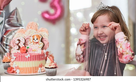 birthday cake for 3 years decorated with butterflies, gingerbread kitten with icing and the number three. meringue pale pink in the shape of a rose or flower. the girl is happy holiday she is happy