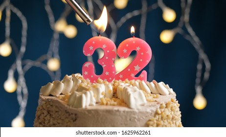 Birthday cake with 32 number candle on blue backgraund set on fire by lighter. Close-up view