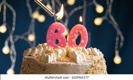 Birthday cake with 60 number candle on blue backgraund set on fire by lighter. Close-up view