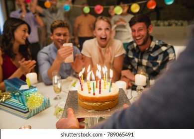 Birthday Cake being brought out to a crowd of people at a birthday party.