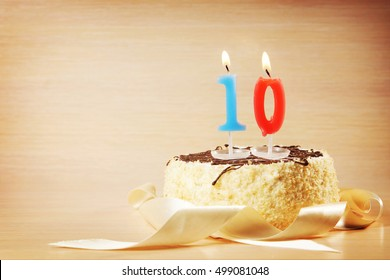Birthday cake with burning candle as a number ten. Focus on the candle
