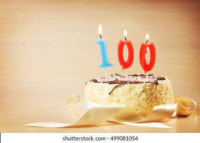 Birthday cake with burning candle as a number one hundred. Focus on the candle
