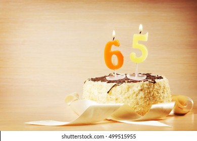 Birthday cake with burning candle as a number sixty five. Focus on the candle