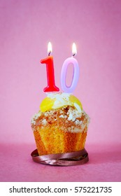 Birthday cake with burning candle as number ten on pink background