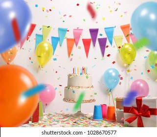 Birthday cake with burning candles against a wall with decoration flags