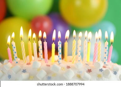Birthday cake with burning candles against blurred background, closeup