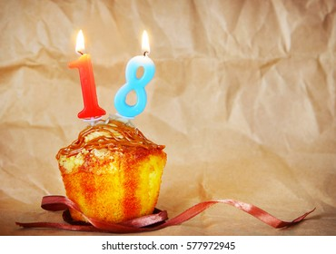 Birthday cake with burning candles as number eighteen on brown paper background