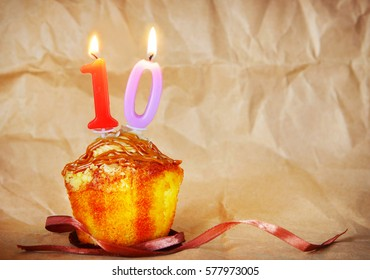Birthday cake with burning candles as number ten on brown paper background