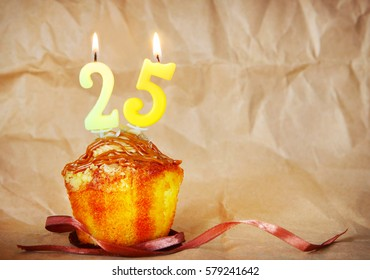 Birthday cake with burning candles as number twenty five on brown paper background