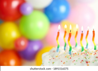 Birthday cake with burning candles on blurred background, closeup. Space for text
