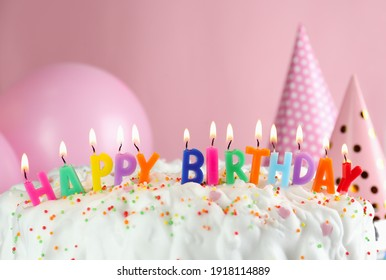 Birthday cake with burning candles on pink background, closeup