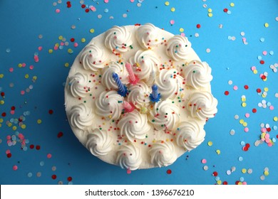 birthday cake with candles for birthday on a blue background with confetti
